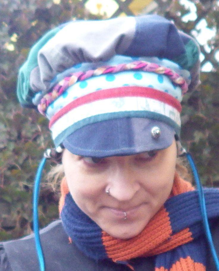 Schirmkappen Beanie mit Ohrenklappen für die kalte Jahreszeit. Aus Babycord im Patchworkstil gefertigt. Bündchen aus Jersey. Geschmückt wurde die Mütze mit einem geflochtenen Jerseyband und einem Metallknopf auf dem Schirm.  Größe 56cm Kopfumfang SM Fadenterror € 45.-