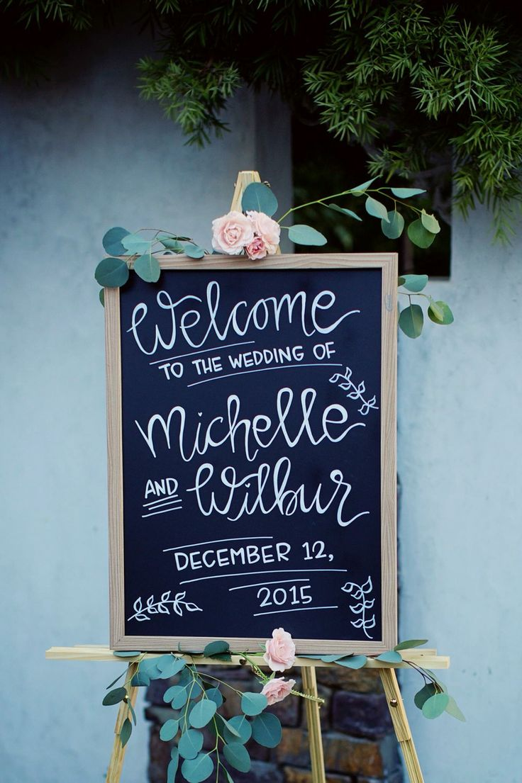 Chalkboard wedding welcome sign with floral accents
