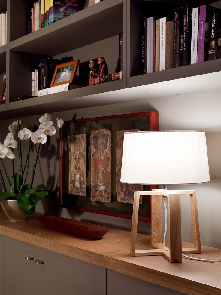 An Designleuchte Faro Bliss bilden die Materialien Textil und Holz eine formschöne Einheit. Zwei Trapeze aus Holz verschränken sich ineinander, um einen stabilen Standfuß zu bilden und tragen eine konisch zulaufenden Textilschirm als Haupt. Wo die Hölzer aufeinandertreffen mischt sich Textilkabel ins Bild, um das Leuchtmittel mit Strom zu versorgen. In dem E27 Sockel sitzen wahlweise energieeffiziente LED oder Halogenlampen, …
