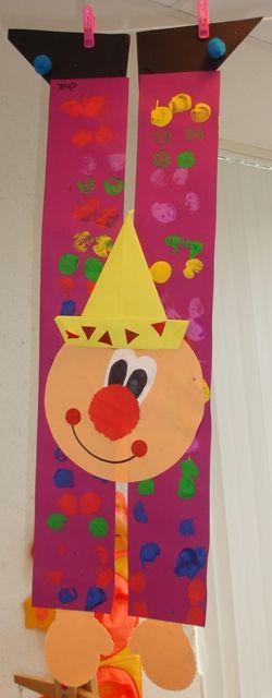 Grote clown op het platte vlak met vouwopdracht Een clown gemaakt van 2 hoedenstroken en een cirkel. De kinderen bestempelen beide hoedenstroken met verf m.b.v. kurken. Daarna knippen zij de mallen van; de mond en de handen (binnenkort online!) uit. Vervolgens knippen zij een zwart vierkant schuin doormidden (de voeten). Het hoedje wordt gevouwen. (van een vlieger).