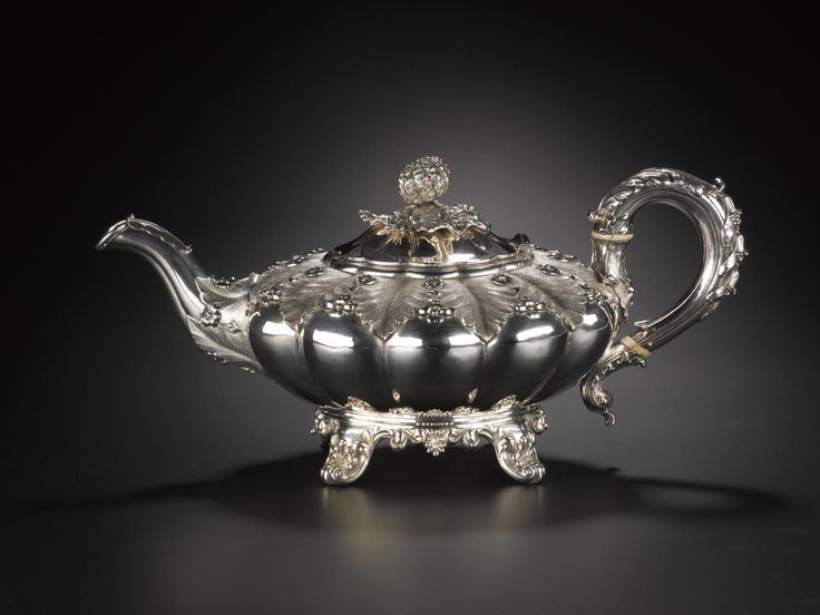 Silver teapot with depressed circular gadrooned body on four feet, and hinged lid surmounted by a knop in form of a fruit, richly ornamented with foliage applied and in relief: English, London, by Edward, Edward, John and William Barnard, 1833 - 1834
