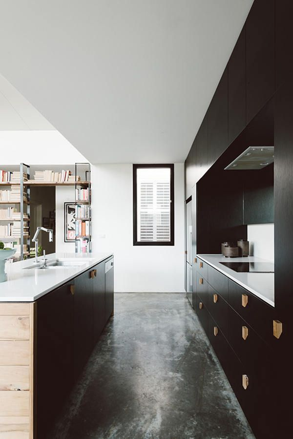 love the saturated black cabinets with custom wooden hardware, alcove for stove, island with contrasting wood and stone :: By Melbourne based design atelier Techné.