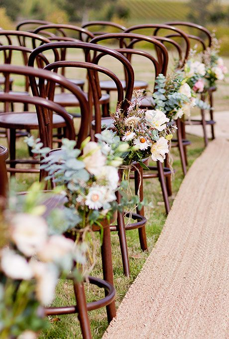 This is such a romantic wedding ceremony look, with a seagrass aisle runner and mixed floral pew ends. Each seat has its own unique mixed bundle of wildflowers, eucalyptus, and roses | Brides.com