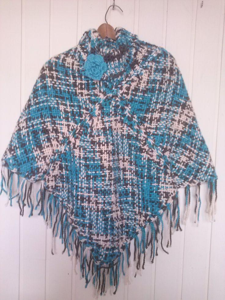 poncho a telar bicolor, con una flor tejida a crochet.