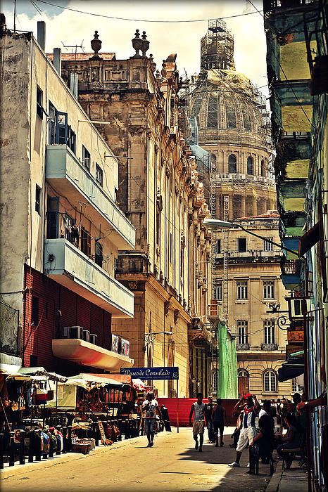 One of the colorful streets of old Havana with view on Capitol.