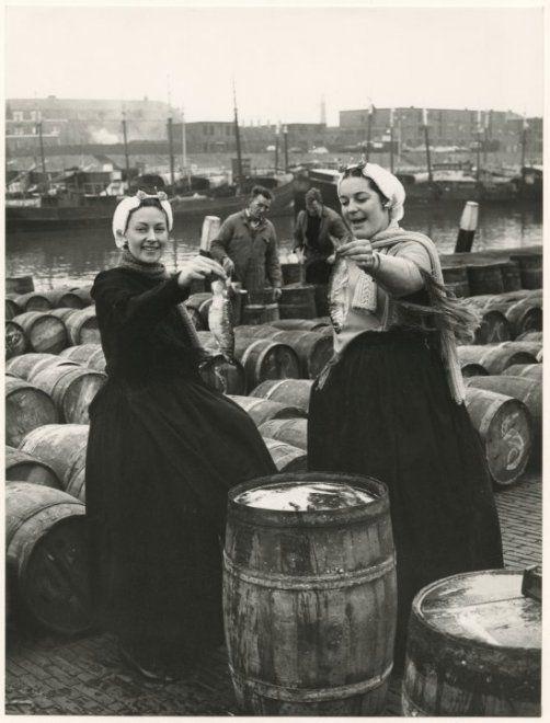 Tweede haven aan de zijde van de Dr. Lelykade, gezien naar de vuurtoren; op de voorgrond twee Scheveningse vrouwen in dracht met een haring in de hand. ca 1965 Fotoburo Meyer #ZuidHolland #Scheveningen