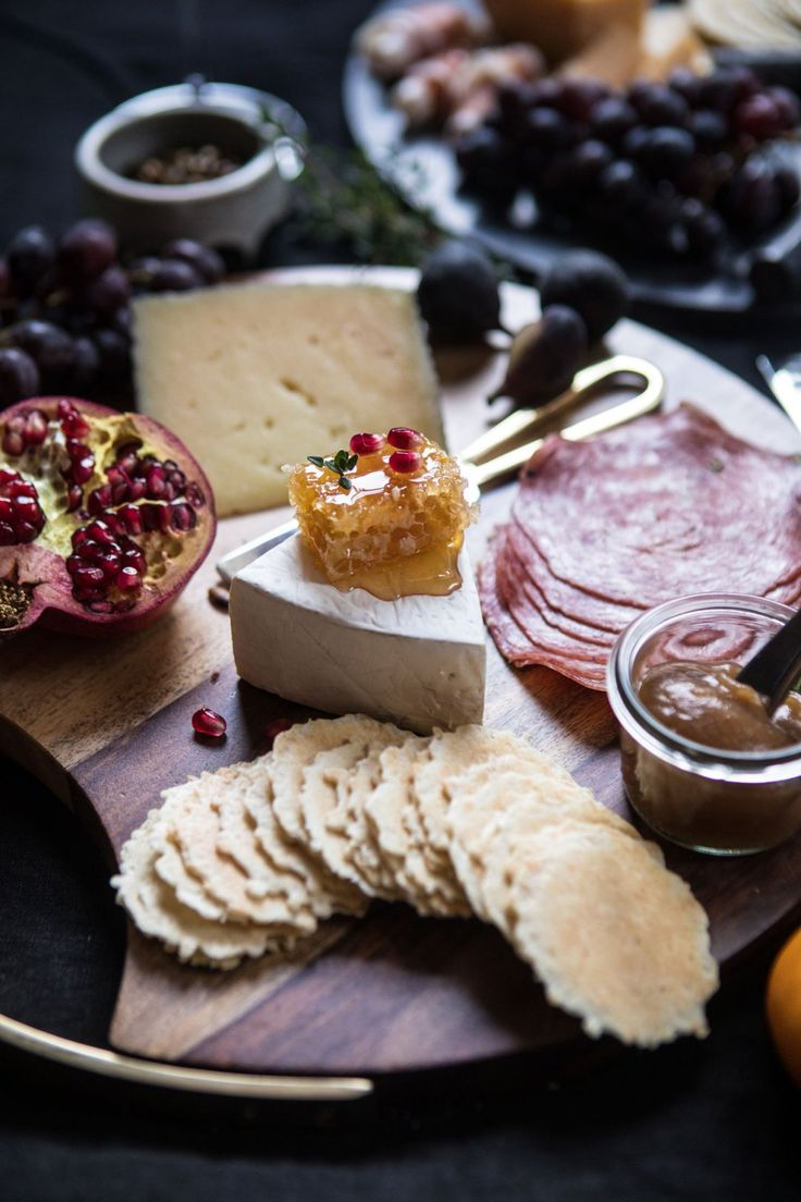 The Spreads: honey, honeycomb, or fruit jam. Fresh Fruits: fresh figs, persimmons, pomegranates, and grapes. Olives and Nuts: olives, roasted salted nuts, and seeds are a great addition to any board. Meats: fresh prosciutto, pepperoni, and salami. Crackers and Bread: