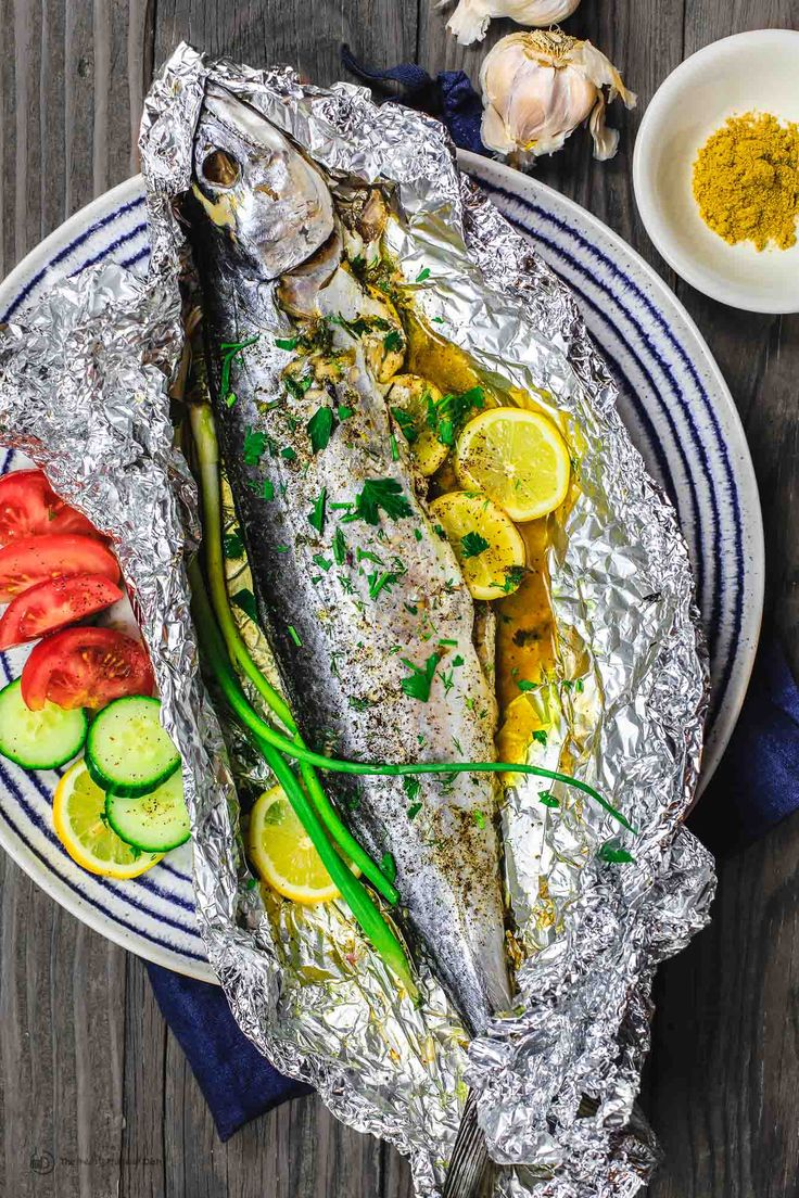 Mediterranean Oven Baked Spanish Mackerel Recipe | The Mediterranean Dish. Easy Greek inspired recipe. Whole fish stuffed with garlic, herbs, and lemon slices and oven baked in a foil packet with olive oil. A delicious Mediterranean diet recipe. See it on TheMediterraneanDish.com