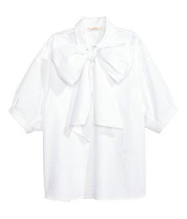 Een wijde blouse van katoenen popeline met een brede, afneembare strikband bij de halsopening. De blouse heeft een kraag, een blinde knoopsluiting boven en korte, wijde mouwen. Afgerond aan de onderkant.