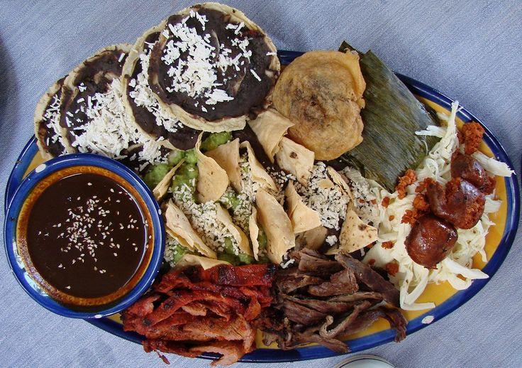 Oaxacan platter: Quesillo, cecina, tasajo, chorizo, pelliscadas, frijoles, guacamole, mole negro, chile relleno, and tamal Oaxaqueno, Mole negro oaxaqueño.