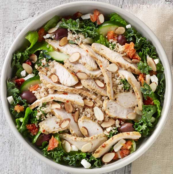 MEDITERRANEAN CHICKEN AND QUINOA SALAD. Bright Mediterranean flavor with a boost from organic quinoa, kale, romaine, cucumbers, kalamata olives, tomato sofrito and toasted almonds in Greek dressing. Topped with chicken raised without antibiotics. Available in whole and half.