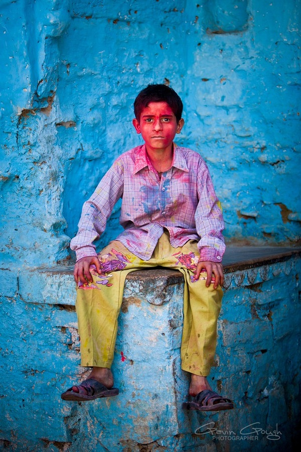 A young boy covered in coloured powder sits in front of a blue wall during colourful Holi Festival celebrations, Radha Rani temple, Barsana, India   Gavin Gough