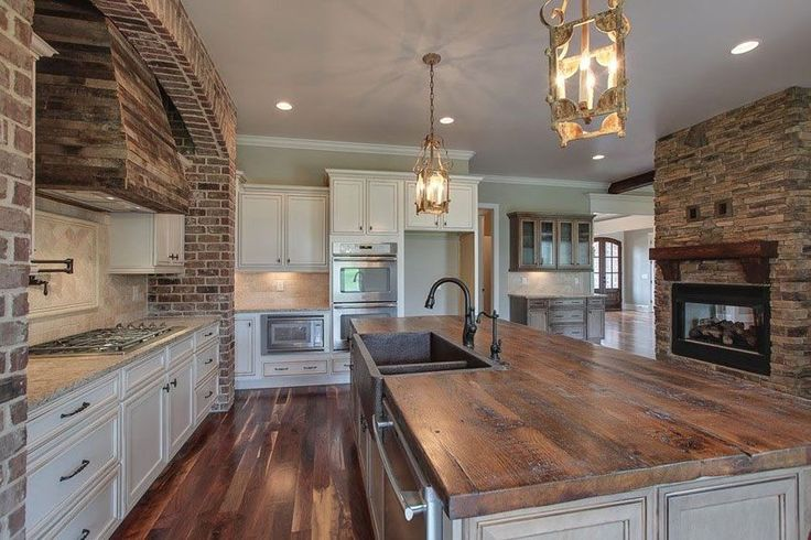 Traditional kitchen with rustic white cabinets, butcher block island and lantern style pendant lighting