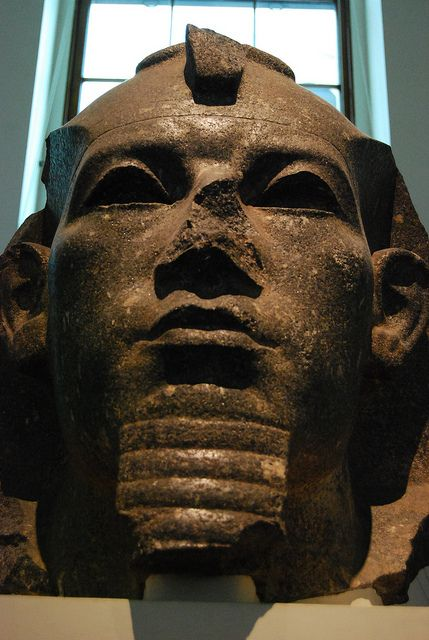 Colossal head of King Amenemhat III, inlaid eyes missing. Once flanked the entrance of Temple of Bastet the cat goddess. It shows the severe style of the late 12th Dynasty ca. 1800 BCE. Bubastis, Egypt