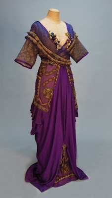 "LUCILE SILK and METALIC LACE BELLE EPOCH GOWN, c. 1912. Trained royal purple charmeuse with short sleeve wrap bodice of gold metallic lace under purple net trimmed with gold fringe and silk flowers, draped hobble skirt with ruffled chiffon side panels heavily appliqued in metallic gold, open at front hem with tassel over chiffon insert, demi-train. Label ""Lucile Ltd 17 West 36th St. New York""."