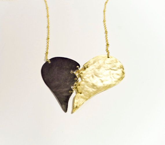 A pendant made of gold and black rhodium plated hammered brass, shaped as broken heart with little chains which are also gold plated by Algo Elegante