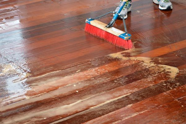 feet and the head of a push broom in use cleaning a wet hardwood deck
