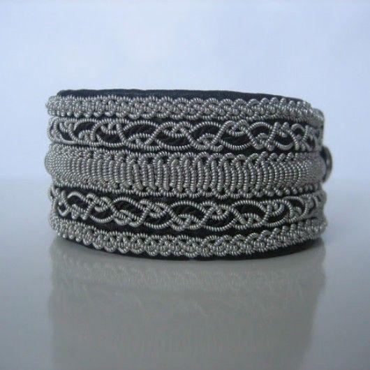 Ett brett snyggt tenntrådsarmband som jag har gjort med lite olika sorters flätor på med tenntråd (4% silver) och svart pärlsilke på svart renskinn. Knapp av tenn