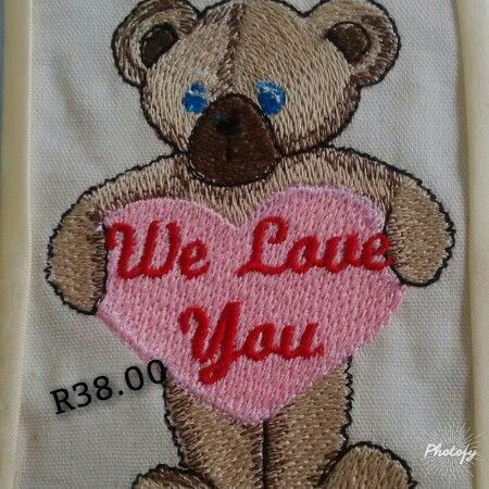A embroidered teddy bear and saying ( We love you )