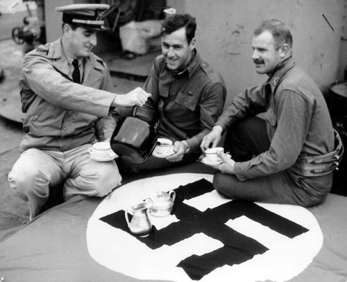 A German flag, captured in Carentan, France, is used as a table cloth while a US Coast Guard officer plays host to two US Army officers at tea aboard a Coast Guard-manned LST off the coast of northern France - 1944