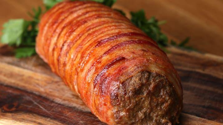 材料:牛ひき肉 1kg卵 2個パン粉 1カップ塩 小さじ2コショウ 小さじ1ガーリックパウダー 大さじ1ハム 4-6枚スライスチーズ 6枚ほうれん草 1カップベーコン 12枚作り方1.オーブンは180 ℃に予熱しておく。2.ボウルに牛ひき肉、卵、パン粉、塩、コショウ、ガーリックパウダーを入れて、肉が白っぽくなるまでよくこねる。3.天板にアルミホイルをしいて(2)を均等に広げる。ハムとチーズを並べてほうれん草をのせ、手前から奥に向かってきつく巻いて、アルミホイルをはがす。4.再び天板にアルミホイルを敷いて、ベーコンを少しずつ重ねながら並べ、(3)をのせて巻く。5.アルミホイルをつけたまま180℃のオーブンで25分焼く。6.アルミホイルを取ってうら返し、オーブンを260℃に上げる。ベーコンに焼き色がつくまで焼いたら、完成!