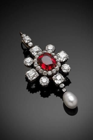 Victorian red spinel, diamond, and pearl pendant/brooch. Set with an oval-cut red spinel to the center, surrounded by circular-cut diamonds forming an oval cluster within a frame of four square and four circular-cut diamonds and suspending an egg-shaped pearl on pendant drop and with a diamond-set detachable top loop, mounted in silver on gold and with detachable brooch pin in fitted case by Harvey and Gore of London, spinel with estimated weight of 5.50cts.