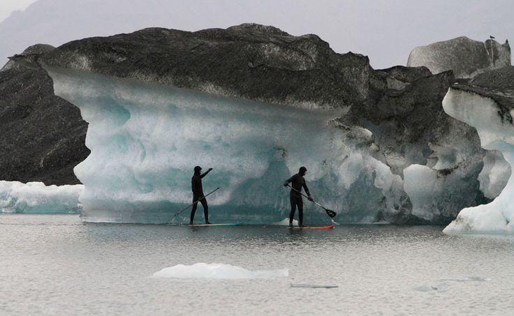 Des surfeurs passent devant des icebergs recouverts de cendre provenant du volcan Grímsvötn …   – Photography