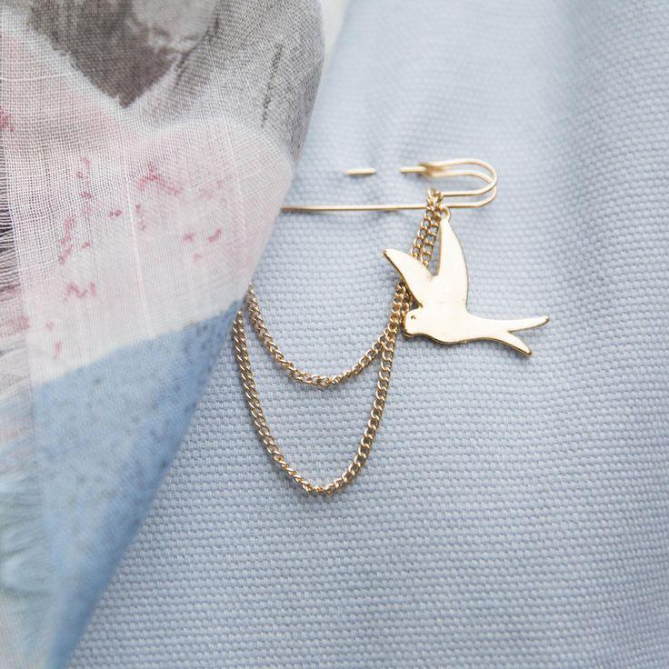 Een mooie broche in de vorm van een kleine kiltspeld, afgewerkt met 2 kettinkjes en een vogelsilhouet. Een elegante oplossing om je sjaal of poncho op z'n plaats te houden.