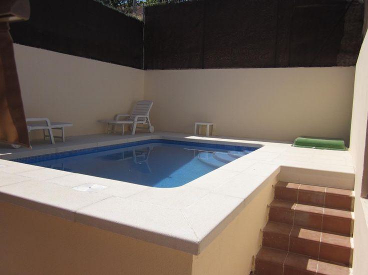 piscina elevada de x con escalera interior romana y gresite color azul cielo