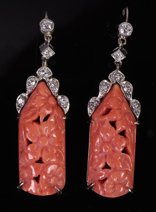 A pair of coral and diamond pendent earrings, the coral drops carved with flower heads, to old cut diamond tops and articulated connections, with fish hook fittings, 4.2cm long overall.