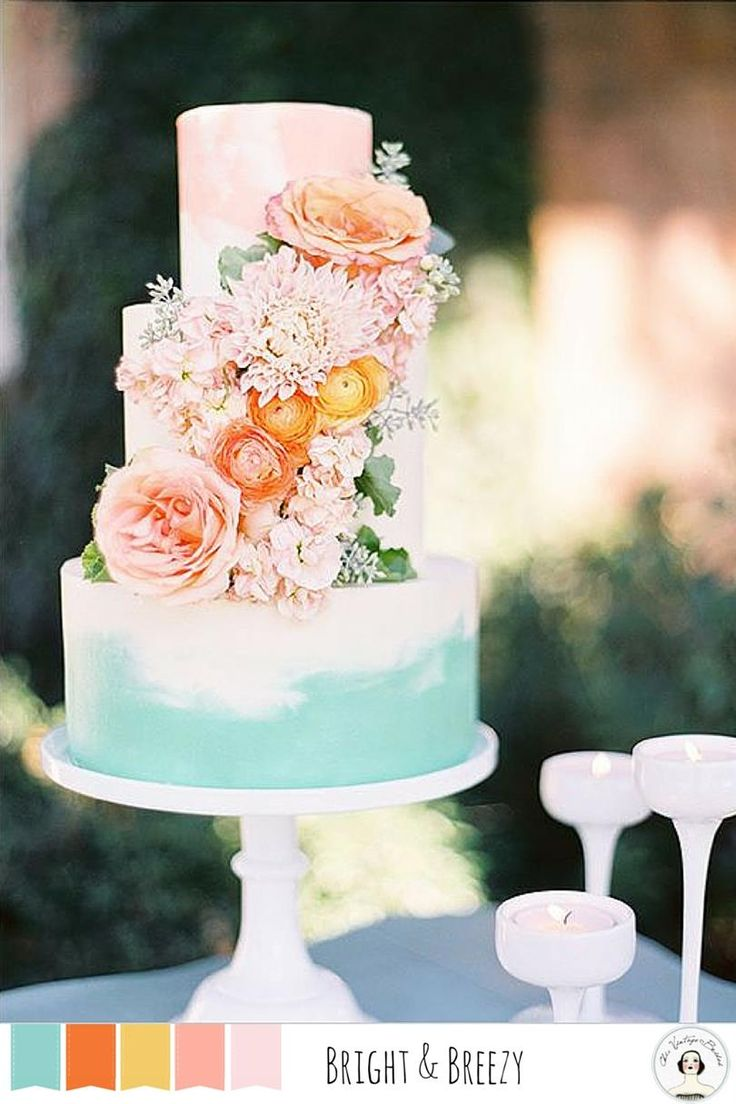 Wedding cake decorated in flowers with a blue watercolor bottom tier