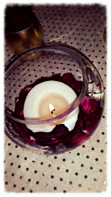 Small fish bowls with candle sitting on Rose petals