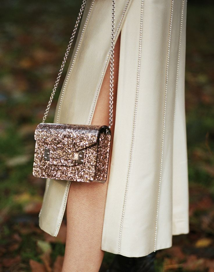 The Compton envelope in pink glitter is crafted in glossy plexiglass. This modern, miniaturised take on the Milner envelope fastens via magnetic snaps. Carry via the gold-plated chain strap, or clasp as a clutch. By night the style adds polish to party looks, by day it adds a playful note to minimal looks.