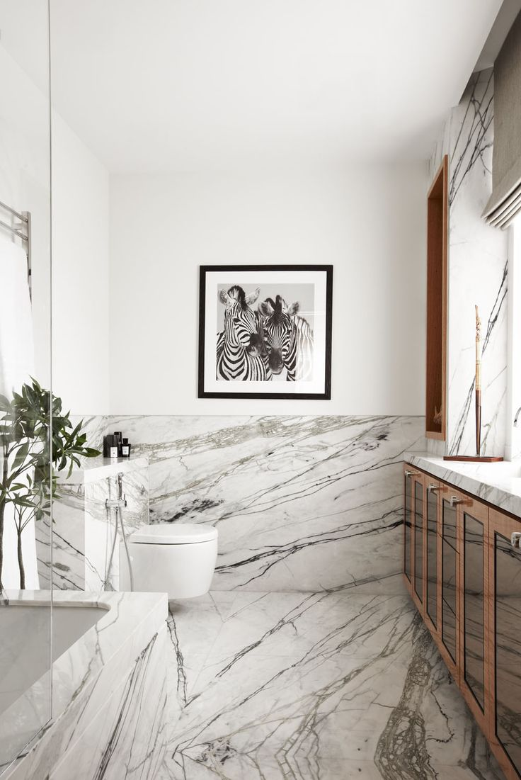 Marble bathroom ideas | White marble bathroom Richly-veined marble in the bathroom can split the space like an artistic statement with  warm wooden cabinets | #bathroomdecor #bathroomideas #marblebathroom