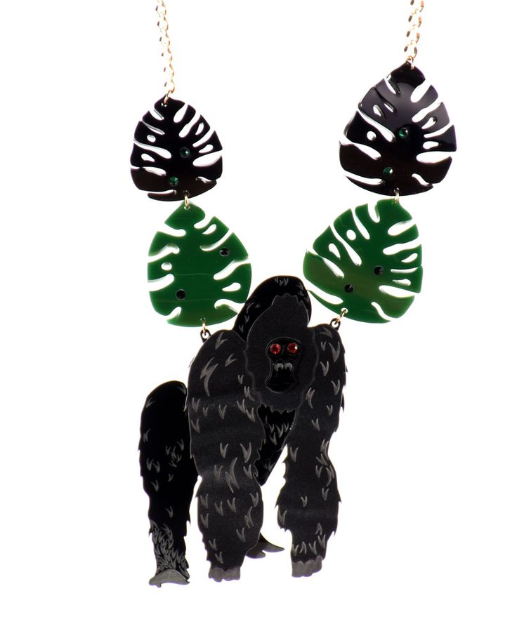 Gorilla necklace,As you are exploring the jungle you feel a pair of intense, reddish eyes staring at you. You grab your binoculars and see a gigantic, intense black gorilla amongst the dense nature, and it won't stop following each of your moves.  Laser-cut etched dark marble acrylic and black acrylic with red swarovski elements, green and black swarovski elements in the bent leaves. Made and assembled by hand.  LIMITED EDITION to 15 pieces.