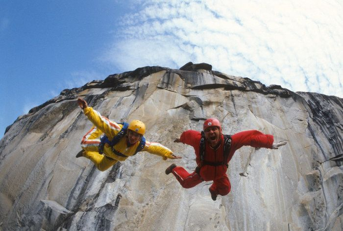 Jean and Carl Boenish in jump down a ledge towards camera.