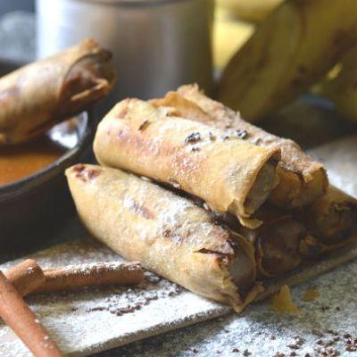 Ζεσταίνουμε το ηλιέλαιο στους 180°C. Τηγανίζουμε τα spring rolls, μέχρι να ροδίσουν. Αποσύρουμε σε απορροφητικό χαρτί. Πασπαλίζουμε με ζάχαρη άχνη και κανέλα. Συνοδεύουμε με τη σάλτσα καραμέλας.