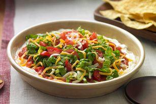 Une couche de fromage à la crème recouverte des meilleures garnitures: salsa, laitue coupée, tomates hachées et fromage Tex…