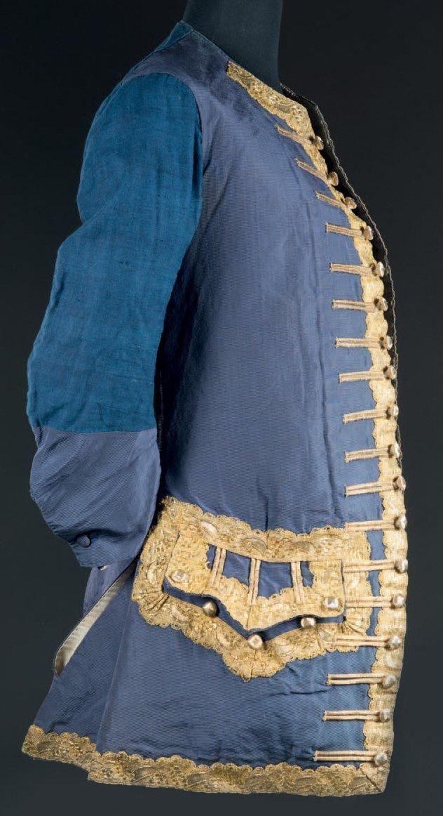 Veste ou gilet d'habit de cour à manches longues, époque Louis XV, vers 1740. Gros de Tours bleu roi souligné d'un large galon et dentelle d'or, boutons ronds en lame d'or, boutonnières fendues, dos et partie non visible des manches en coton teint à l'indigo. H: 76 cm (bel état)