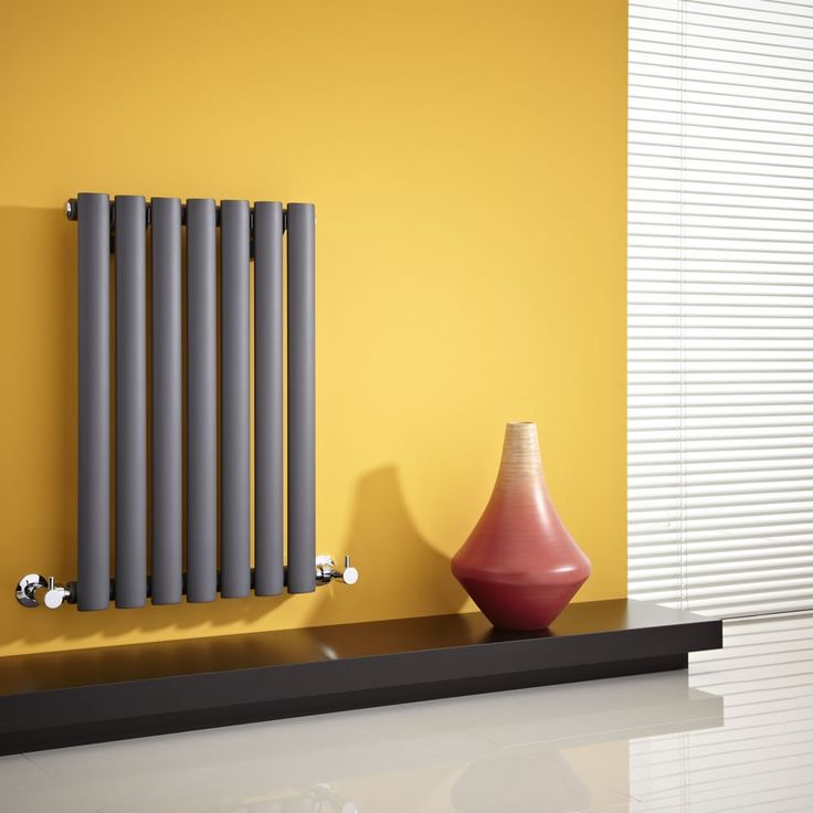 The Milano Aruba 635mm x 415mm horizontal radiator in anthracite looks great against the yellow wall.