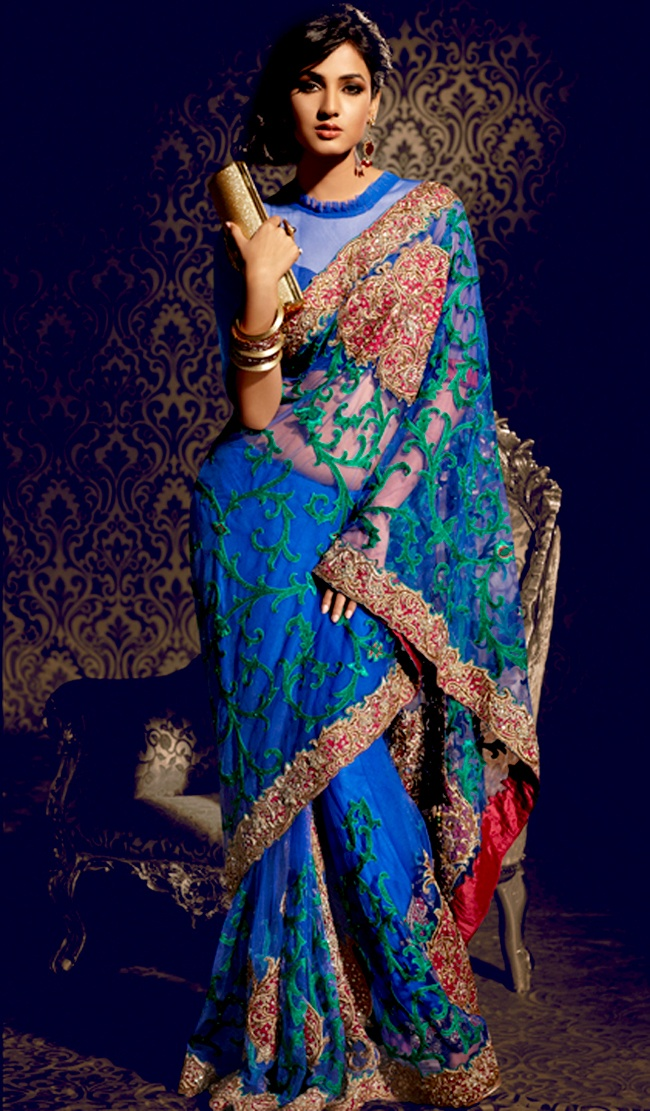 Attract all attentions with this embroidered saree.   This blue net saree is nicely designed with embroidered patch work is done with resham, zari, stone and lace work.   Beautiful embroidery work on saree make attractive to impress all.   This saree gives you a modern and different look in fabulous style.   Matching blouse is available.   Slight color variations are possible due to differing screen and photograph resolution.