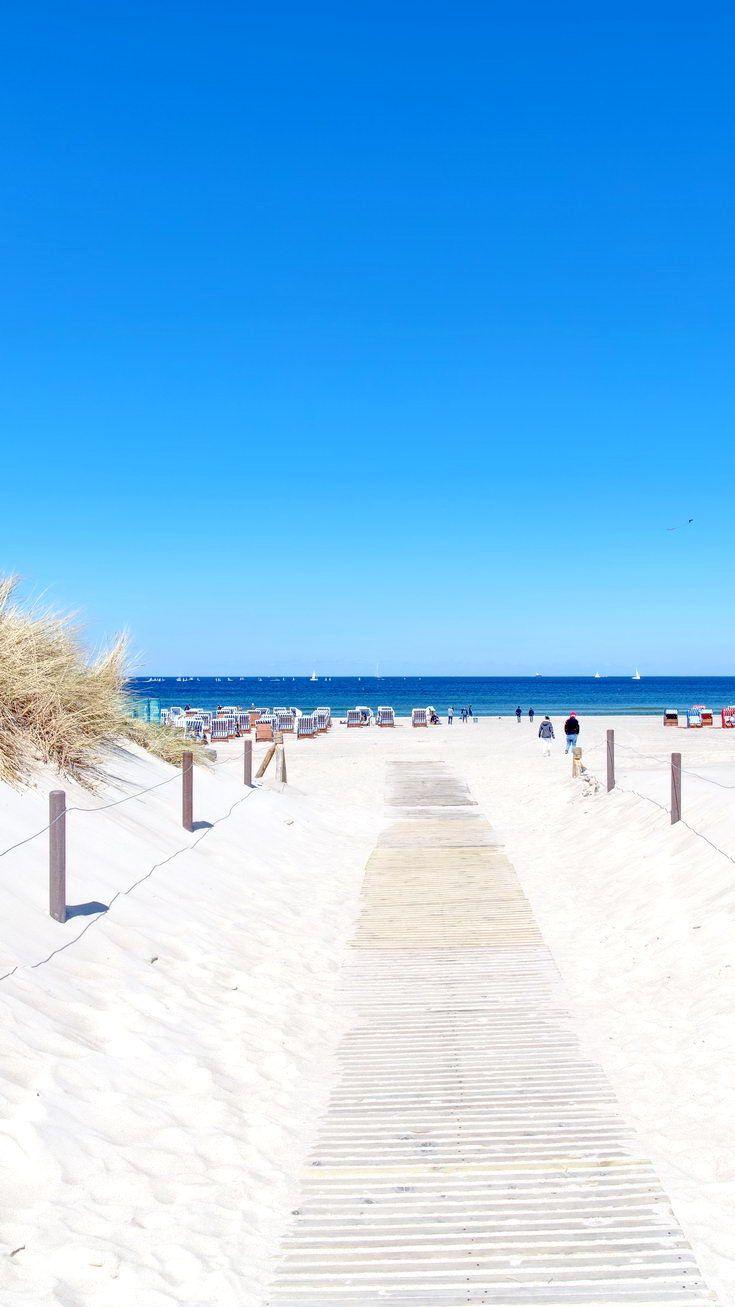 Holzweg am Strand von Warnemünde. Blauer Himmel i…