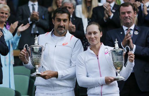 Nenad Zimonjic of Serbia and Samantha Stosur of Australia hold their trophies after defeating Max Mirnyi of Belarus and Hao-Ching Chan of Taiwan in the mixed doubles final at the All England Lawn Tennis Championships in Wimbledon (AP)