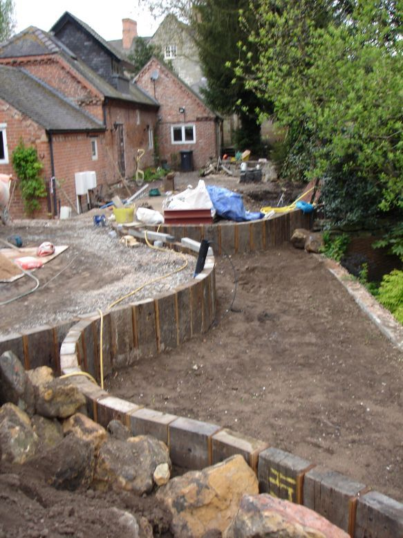 railway sleepers using vertical sleepers to make retaining wall on a slope gardening in lights
