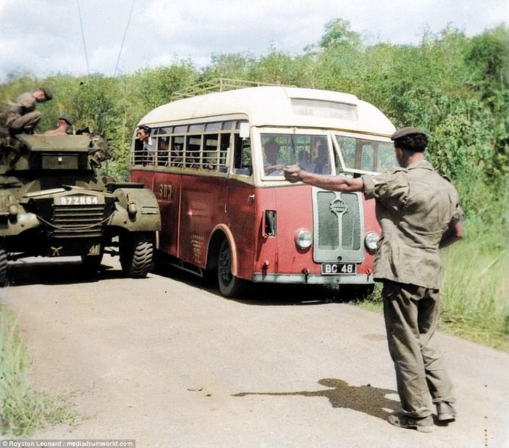 A soldier directs a bus, which has pulled up alongside a tank. The conflict was labelled as an 'emergency' because insurers would not have compensated plantation and mine owners, whose livelihoods were under attack from communist insurgents, had it been labelled a 'war'