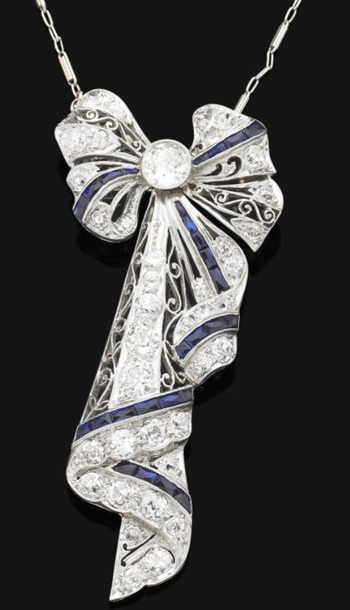 A Belle Epoque sapphire & diamond pendant/brooch, ca 1918.  The pendant/brooch modelled as a stylized bow, set with a central old brilliant-cut diamond, to the pierced diamond-set ribbon mount, accented by french-cut sapphires, with fine-link neckchain, pendant/brooch mounted in platinum, chain mounted in 14 ct white gold, central diamond weighing approx 0.60 ct, remaining diamonds approx 1.50 cts total, pendant/brooch length 6.5cm, chain length 55.0cm.