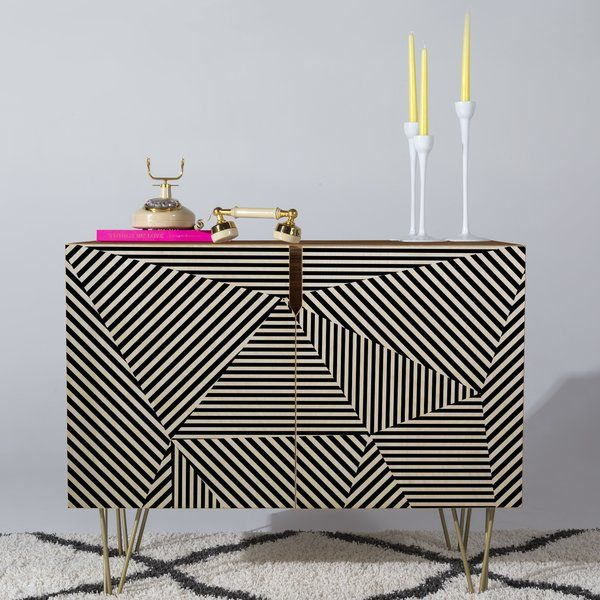 Add a touch of modern sophistication to your ensemble with the Corbin Credenza, featuring abstract geometric cabinet door fronts and a neutral finish. Set it in your dining room to fill it with simple ceramic serveware and plates, then top it off with a vignette of abstract statuettes and shimmering chrome candle holders to tie your ensemble together in eclectic style. For a dash of midcentury appeal in the living room, set this with clean-lined arm chairs and sofas around the space, then…