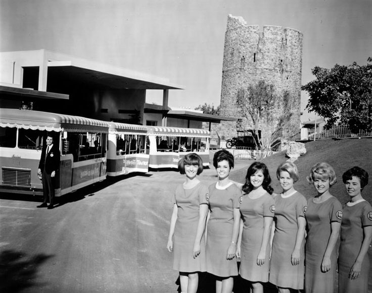 "Trams Departs from new 1965 Entertainment Center , Universal City Studios   [photo]""Cheese!"" These six smiling beauties are part of the Universal City Studio Tour Guide Corps. The GlamorTram in background is one of many used to transport studio visitors around the 410-acre movie lot."