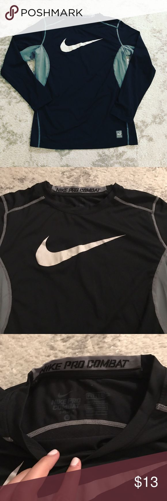 Black & gray Nike Pro Combat fitted shirt Black fitted Nike Pro Combat long sleeve shirt with gray stitching and gray mesh sides. White Nike swoosh logo screened on the front of the shirt in white. This is a Boys' Large, but could probably fit a Women's Small. This shirt is worn (see photos of Nike swoosh), but there is still a lot of life left in it! Nike Shirts & Tops Tees - Long Sleeve