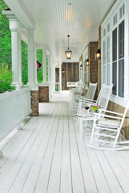 long porch with white rocking chairs
